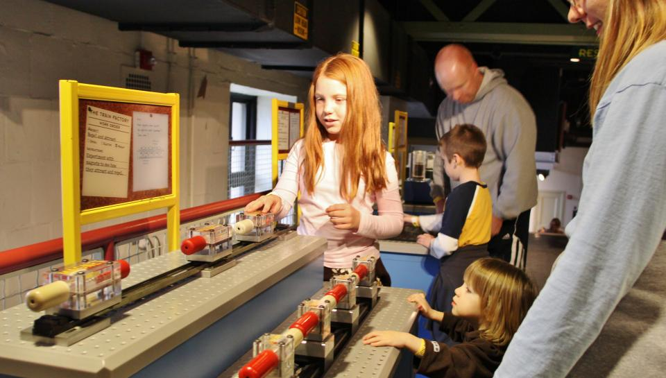 girl plays with model trains