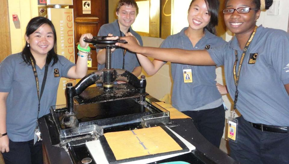 Franklin Institute volunteers posed around the Papermaking Cart.