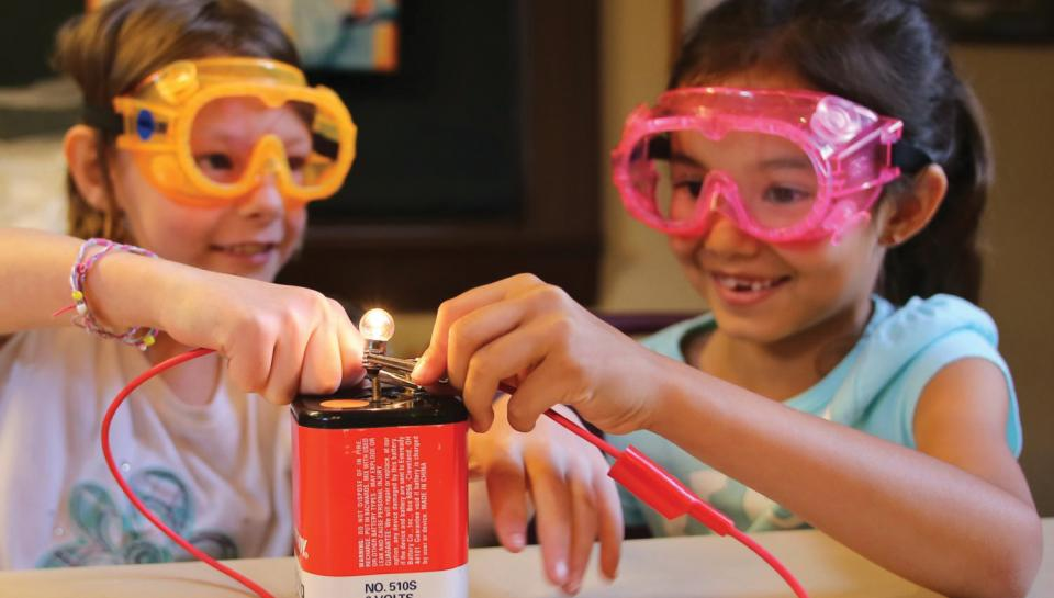 Kids with light bulb and battery trying to generate electricity