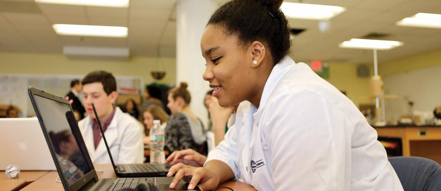 A teenage girl from SLA working on a laptop and smiling.