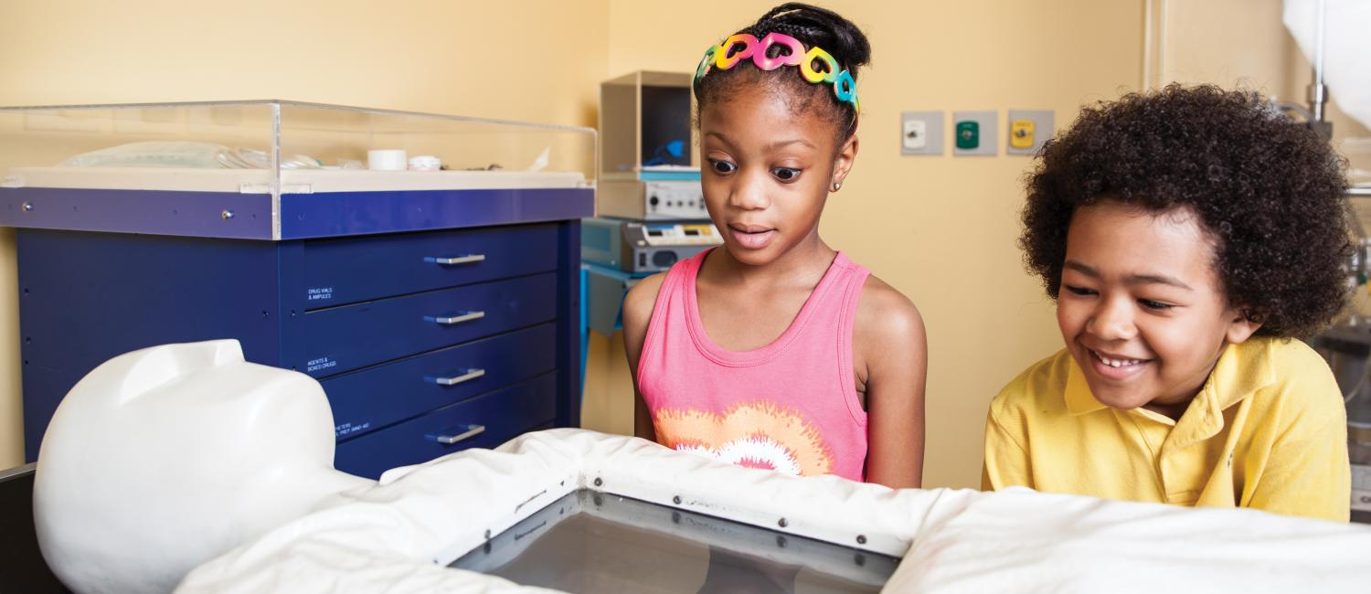 Young girl looking shocked and surprised at the open heart surgury video in The Giant Heart.
