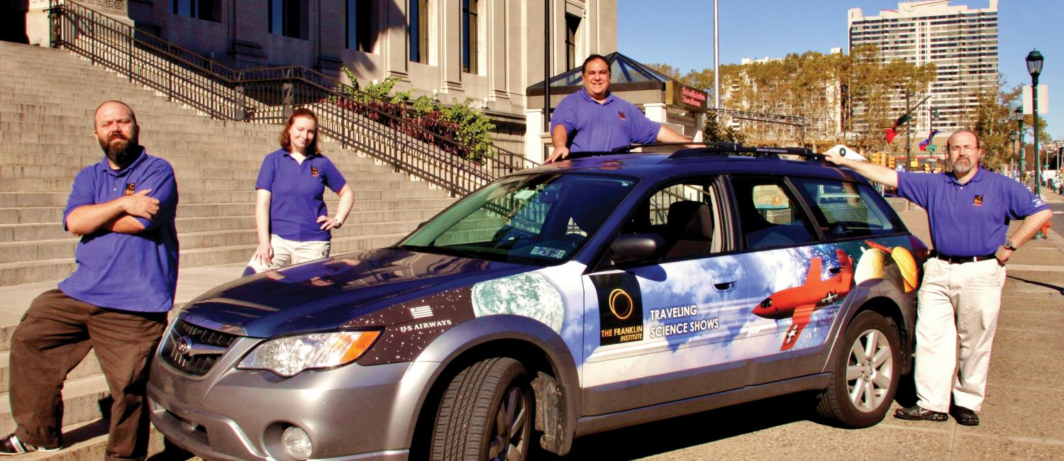 The Traveling Science staff posing with the TSS car in front of the steps of The Franklin Institute.