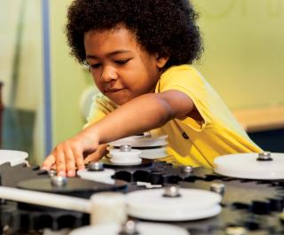 A young boy is contemplative as he reaches for another gear on the interactive, Design Challenge in the permanent Franklin Insitute exhibit, Amazing Machine.