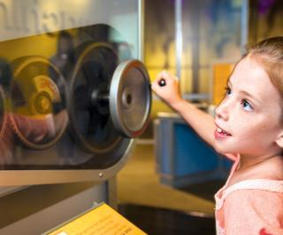 A young girl uses a crank to test the difference between gear size and speed in the exhibit Amazing Machine.