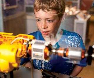 Another young boy is surprised and intrigued by the inner workings of an electric drill in the exhibit Amazing Machine.