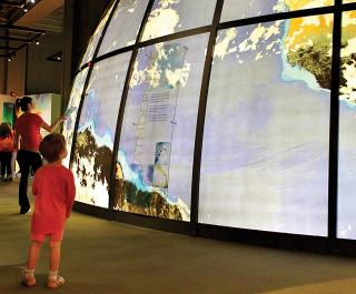 Visitors enjoying the permanent exhibit, Changing Earth. The giant globe in the center of the exhibit can be seen prominently.