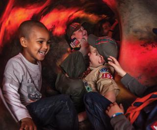 Boy scouts laughing and having a great time in the Changing Earth exhibit.