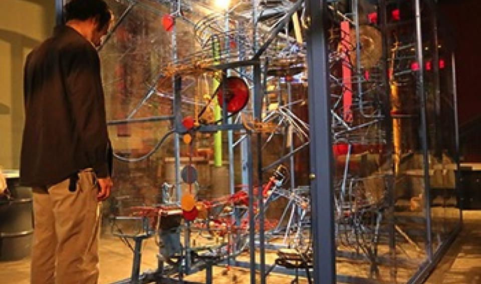 Photo of adult looking at the perpetual motion machine in Sir Isaac's Loft