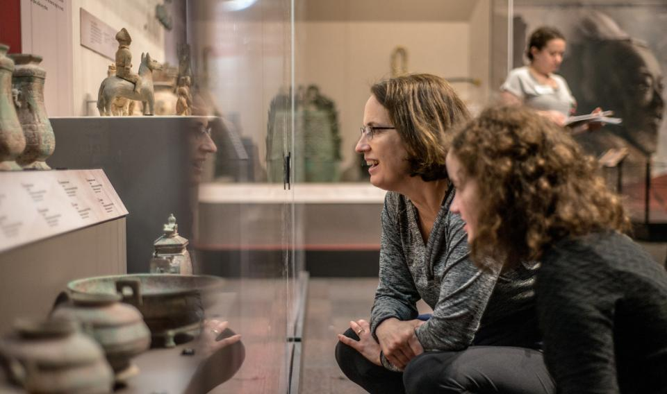 A woman and a girl looking into a display case