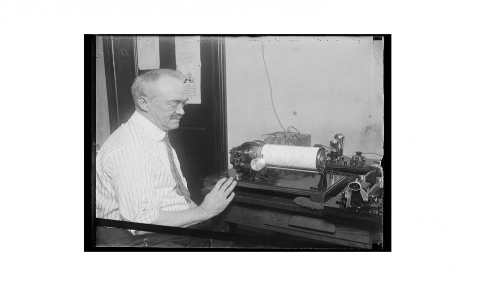 Black and white historical photo of Francis Jenkins in front of machine