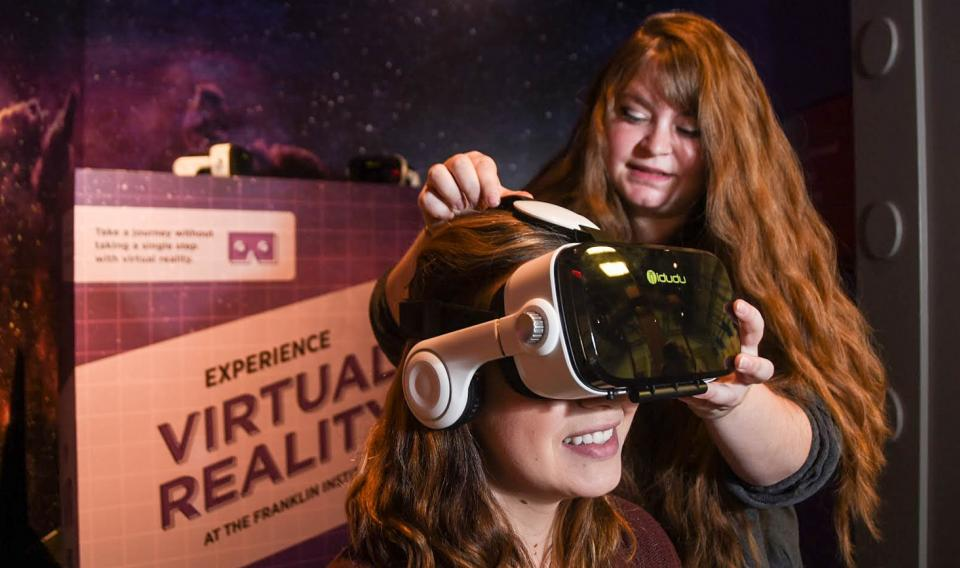 Museum staff member helping a guest experience virtual reality through a headset at the Franklin Instutute