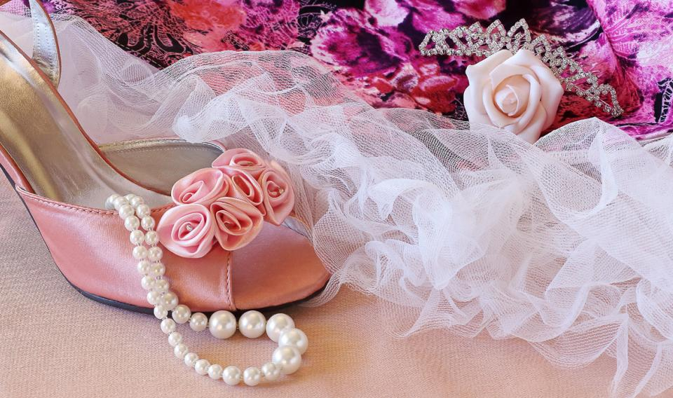 Photo of pink prom dress, pearls, shoes, tiara and flowers
