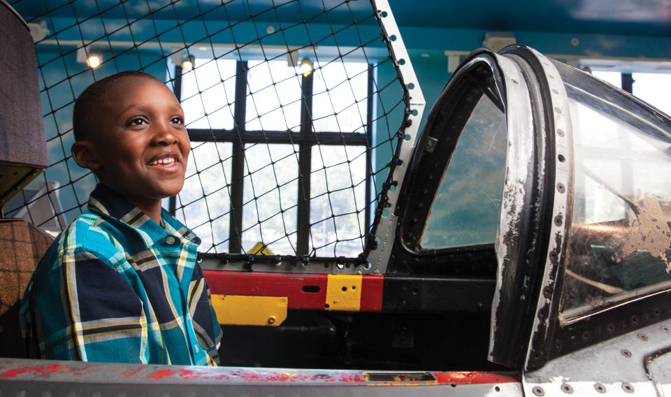 A young boy sits in the cockpit of the plane that hangs from the ceiling in the permanent exhibit The Franklin Airshow