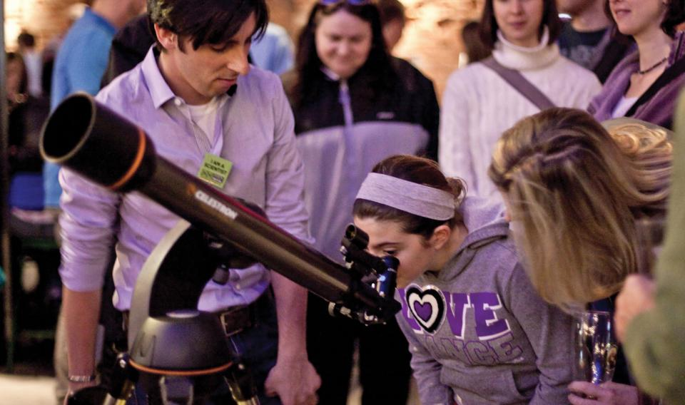 A girl looking through a telescope during a City Skies event through The Franklin Institute.