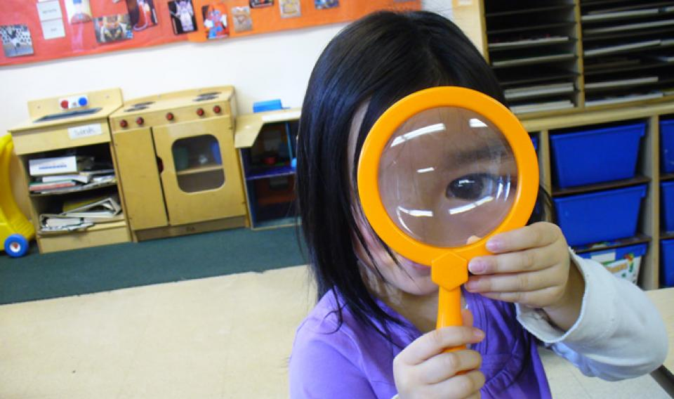 A little girl holding up a magnifying glass during a Traveling Science Show from the Franklin Institute.