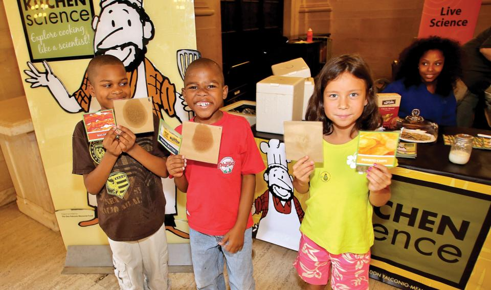 Kids at a Kitchen Science table, holding up examples of different foods that are greasy.