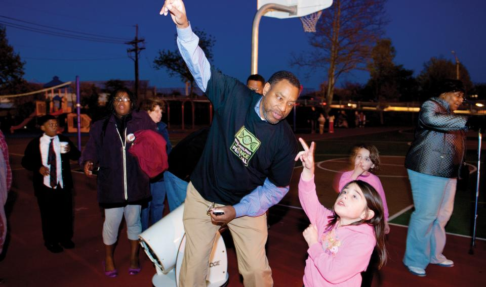 Chief Astronomer Derrick Pitts from the Franklin Insitute teaches a young girl about space.