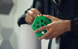 Somebody examining a piece of a telescope that was 3D printed