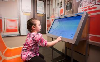 A young girl using the Say That Again interactive in the Your Brain exhibit at The Franklin Institute.
