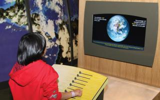 A kid learning about their carbon footprint in the Changing Earth exhibit at The Franklin Institute.