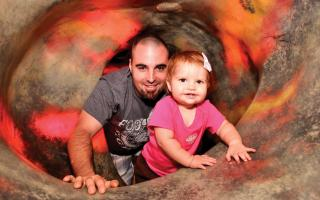 A father and his baby daughter crawing through the magma tunnel at The Franklin Institute.