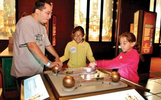 A family completing an electrical circute in the Electricity exhibit at the Franklin Institute.