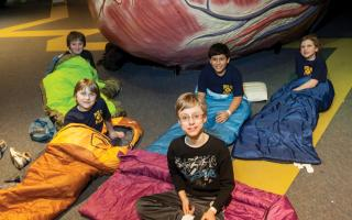 Five boy scouts in their sleeping bags infront of The Giant Heart during a Camp-In event at The Franklin Institute.