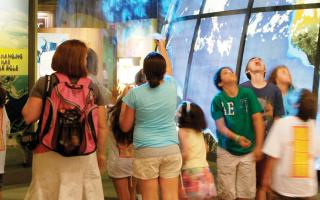 Entrance to The Franklin Institute's Changing Earth exhibit is filled with visitors entranced by the vapor earth image.
