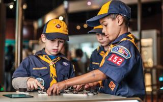 Three boy scouts learning about electric circuts in the Electricity exhibit