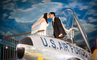 Newlyweds kissing on top of an airplane exhibit.