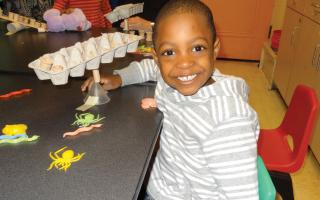 Young child exploring balance in a LEAP into Science preschool workshop from The Franklin Institute.