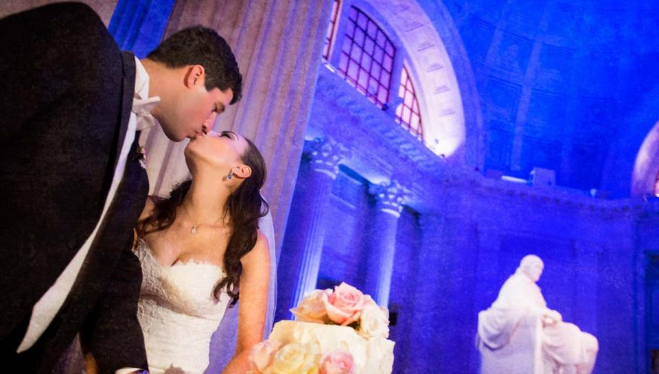 Newlyweds kissing in front of the Benjamin Franklin Memorial at The Franklin Institute.