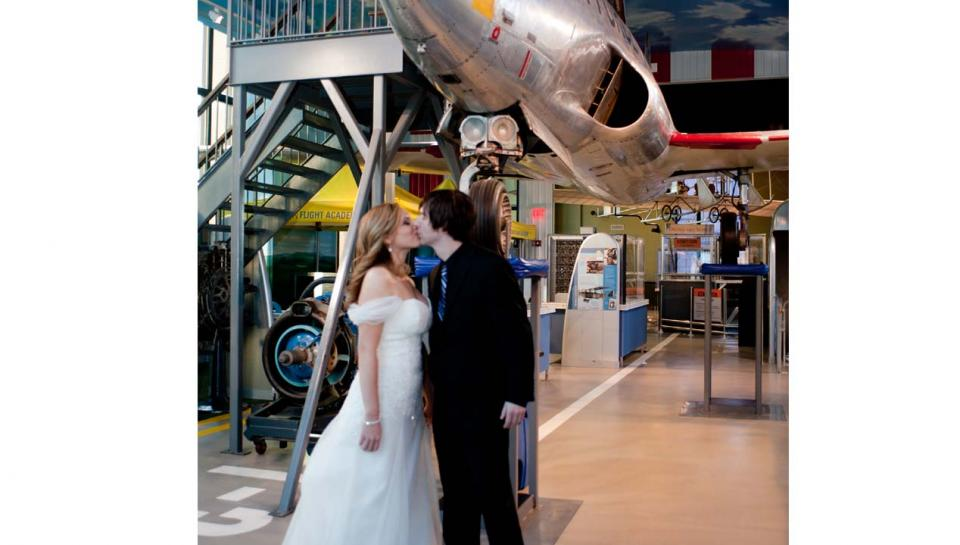 Newlyweds kissing in the Franklin Airshow exhibit at The Franklin Institute.