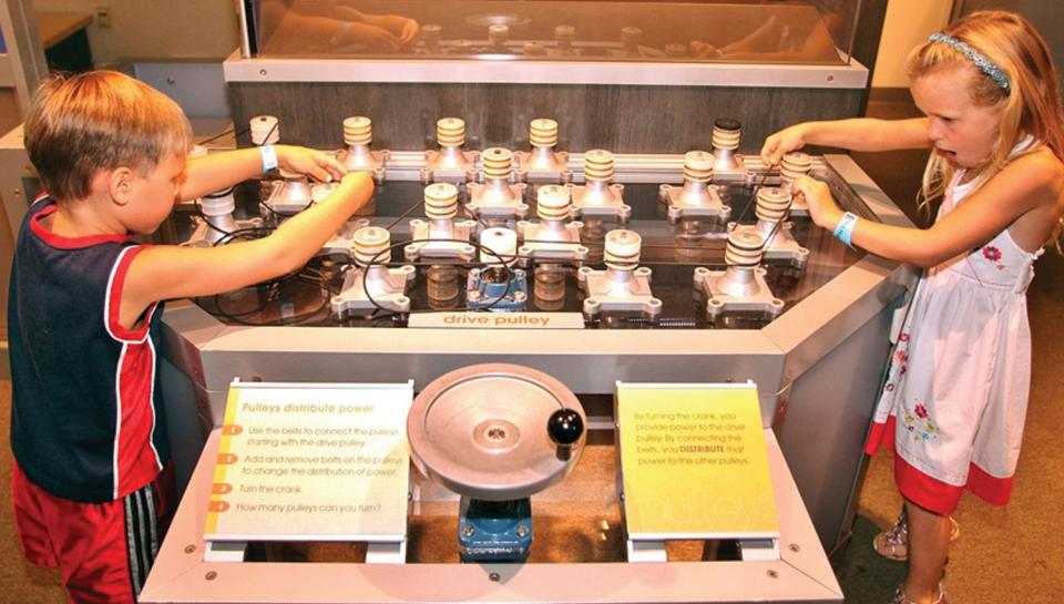 Two children learn the science behind pulley systems in the Amazing Machine exhibit.