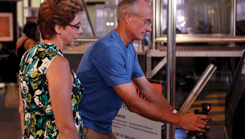Two adults enjoying piloting interactives in The Franklin Air Show exhibit.