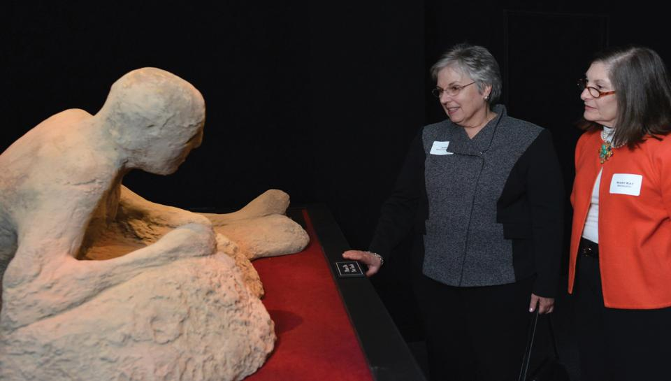 Guests inspecting human remains mummified in ash in the One Day in Pompeii traveling exhibit at The Franklin Institute.
