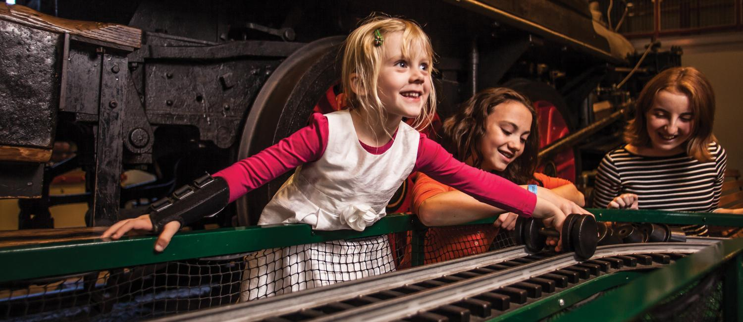 Young kids learning about trains in the Train Factory exhibit.