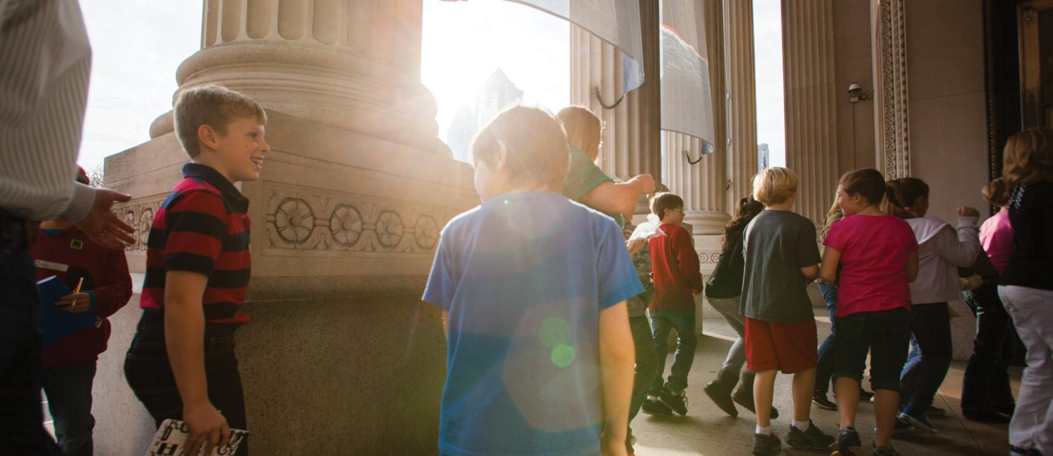 Visitors entering the museum's front doors at sunrise.